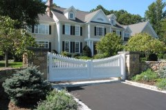 Designed Front Gate and Stone Wall Along With Surrounding Plantings
